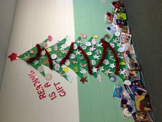 """""""Reading Is a Gift"""" Christmas display for library or language arts. Christmas tree is cut from green bulletin board paper. Die cut letters from wrapping paper. On traditional ornament shapes from copy paper, students write a sentence expressing the importance of reading, then decorate with markers, colored pencils, and glitter glue."""