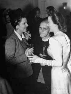 Carole Landis talking with fellow actress Kay Francis about her wedding ceremony as the Cleric listens.