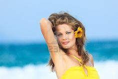 Beautiful woman in yellow dress on the beach Stock Photo