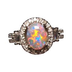 Beautiful natural Lightning Ridge Semi Black Opal ring with round and baguette Diamond accents. #opalsaustralia