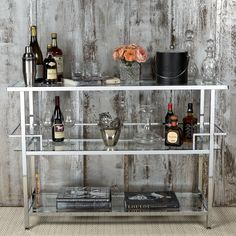 Features:  -Chrome plated steel frame for durability.  -3 Clear glass shelves.  -Spill guard around center shelf.  -4 Floor levelers for stability.  Product Type: -Home bar.  Style: -Glam.  Bar Shape: