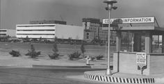 View from Lindley Avenue entrance of San Fernando Valley State College (now CSUN) campus -- 1963. In the foreground is the information booth available to assist motor vehicle traffic. In the background, the campus' first permanent library (later known as the South Library) is clearly visible; just behind that, construction of Sierra Tower can be seen. CSUN UNiversity Digital Archives.