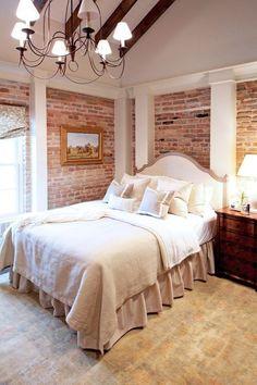 Exposed brick! Love the bedroom furniture!  columns!