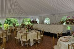 """Fairy Tale Tents & Events - Frankfort, IL - 40'x40' High-Peak Fairy Tale Frame Tent with cathedral window side walls, white side pole swags with white ties, and full tent flooring; 60"""" round tables with ivory polyester table linens, ivory Antoinette overylays, ivory polyester napkins, gold charger plates and gold chiavari chairs and ivory chair pads; 12 person head table on risers with ivory lamour satin gathered skirting with brooches"""