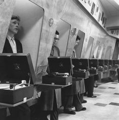 Customers at a London music store listen to the latest record releases in soundproof listening booths, 1955.