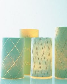 Stitch a delicate pattern (you can use one of our templates) onto a sheet of card stock. Then wrap around a glass cylinder for the candlelight to flicker through.