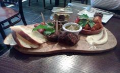 Sharing Plate @ Greens Vegetarian Restaurant, Manchester - black pudding, patatas bravas, mini smoked cheese sausages served with bread, salsa verde & marinated olives.