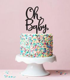 multicolored sprinkles covering a tall cake, placed on a white ceramic cake stand, and decorated with a topper, saying oh baby