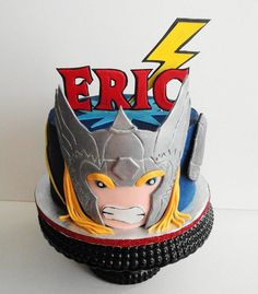 The Thor Cake. Part of three cakes I did with an Avenger theme for two little boys.  Cake is chocolate with fresh strawberry filling, chocolate buttercream with a couple of thin layers of blue buttercream topping it to give it the blue background.   Hand cut gum paste letters, silver helmet and lightening bolt.   Fondant face and hair.  I used silver luster dust on grey fondant for the helmet.