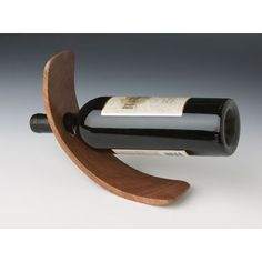 Curved Wood Wine Bottle Holder is a unique curved wine bottle holder made of wood that holds a bottle of wine in perfect balance. The Curved Single Wine Bottle Holder is made of Agathis, a subtropical pine wood Wood Wine Bottle Holder, Bottle Rack, Wine Bottle Crafts, Sauce Bottle, Personalized Wine Bottles, Wine Stand, Bottle Display, Curved Wood, Wine Storage