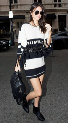 Kendall Jenner wears a fringe sweater dress with ankle boots and aviators.