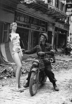 A Canadian dispatch rider somewhere in Normandy strikes a match on a mannequin's hip. Alex Gray took this human-interest shot, hoping that this dispatch rider's home-town paper might run it.