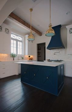 Navy blue island and hood with beautiful gold pendants. Timeless Kitchen Casiewebbdesigns  Ketteringham Builders
