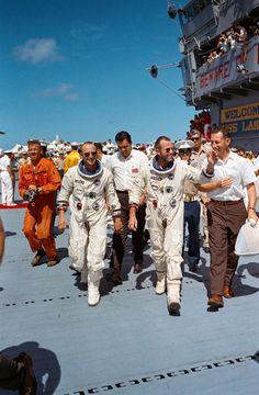 Two astronauts in flight suits walk across carrier deck, waving