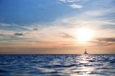 A sailboat in the distance breaks a colorful skyline