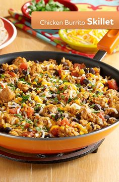 Chicken black beans zesty tomatoes and taco seasoning cooked together with brown rice for an easy burrito skillet topped with cheese.