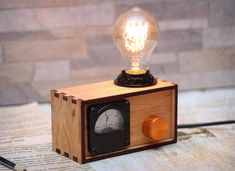 Birch plywood box, Edison bulb and Soviet voltmeter. Lamp box created from birch plywood. Polished and smoothed by hands. Coated linseed oil and beeswax. The product has a USSR voltmeter (1970s). The device is in working and shows voltage mains. This lamp has a dimmer for incandescent