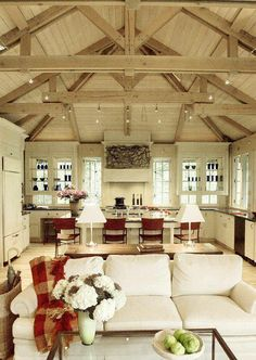 The idea is right: Lots of white, exposed beams, mix of rustic elements and new with a farmhouse feel. Yes. Except that crazy artwork above the stove.