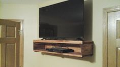 This is a wall mounted TV Stand with a place for your DVD or Blu Ray player. It uses 2 lag bolts to mount on the wall. It can be stained or