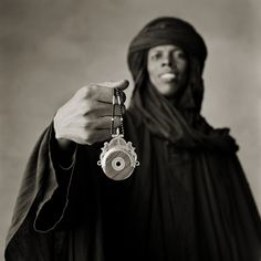 Tuareg man holding up an astrolabe-inspired pendant, strung on a beaded necklace. The clear desert skies allowed the Tuareg to be keen observers. Tuareg celestial objects include: Amanar (Orion), the warrior of the desert. Azzag Willi (Venus), which indicates the time for milking the goats. Shet Ahad (Pleiades), the seven sisters of the night.  Talemt (Ursa Major), the she-camel wakes up. Awara (Ursa Minor), the baby camel goes to sleep. Niger, Sahara.