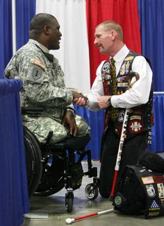 (Steve Griffin / The Salt Lake Tribune) Iraq War veteran Gordon Ewell, right, of Eagle Mountain, Utah, shakes hands with Col. Gregory D. Gadson, who is with the U.S. Army Wounded Warrior Program, as they talk during the Utah Veterans and Families Summit at the Salt Palace Convention Center in Salt Lake City, Utah Friday March 30, 2012.