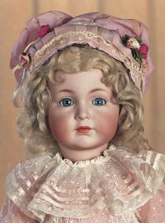"""21"""" (55 cm.) Marks: K*R Simon & Halbig 117 55. Comments: Kammer and Reinhardt,the gentle-featured model was a transitional doll between their art character series and classic dolly series,circa 1912. Value Points: most endearing expression is enhanced by fine quality of bisque and painting,original body and body finish,beautiful antique lace and rose cotton costume,undergarments,leather shoes."""