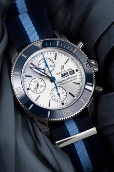 The Breitling Superocean Heritage II Chronograph 44 (Ref. A133131A1G1W1) comes with a 44 mm case and is water-resistant to a depth of 200 meters. With its silver dial, a day and date display, an automatic calibre, a blue bezel as well as a blue textile strap, this chronograph has an unusually fresh and juvenile appearance. A refreshing twist on the Breitling line-up. Breitling Superocean Heritage, Breitling Watches, Chronograph, Display, Fresh, Luxury, Water, Silver, Blue