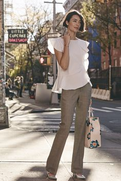 Natalia Costa is chic and sophisticated in our menswear inspired Logan trousers. These structured gray lightweight wool pants are perfectly paired with a soft white striped blouse, floral tote and silver pointed-toe pumps | Banana Republic
