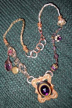 Using a vintage  stamping and my grandmothers broach (vintage) that was attached using copper wire make the striking pendant. Soldered to the back hand tooled copper rings for the neck chain to extend from.  Other charms and metal ribbon make up the neck piece.   beadlishous@yahoo.com