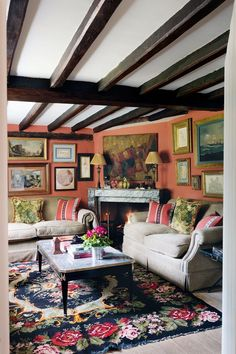 A nineteenth-century French chimneypiece anchors the densely hung pictures and the symmetrical seating in the sitting room