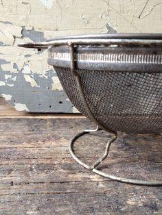 Vintage metal colander with wire foot