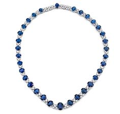 Oval Sapphire and Diamond Riviere Necklace---   Oval-shape sapphires graduate in size along this necklace, spaced with floral clusters featuring five diamonds in each station. 18k white gold 33 sapphires, 59 cts. t.w. 18 diamonds, 11.84 cts. t.w.     SKU JNK155     Brand Joshua J     MSRP $98,818.00