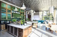 A huge gourmet kitchen has pressed tin ceilings, cement tile floors in a graphic pattern, large pendant lights, a breakfast nook and a sitting area  surrounded by floor to ceiling encasement windows. (above)