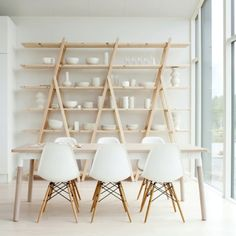 angled wood shelves displaying white objects in a slightly soulless white room, daylight pouring in
