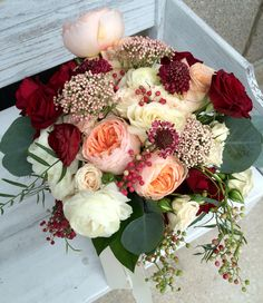 Bridal bouquet featuring blush garden roses, ivory and burgundy spray roses, white ranunculus, light pink rice flower, and burgundy scabiosa blooms, accented with flowing red pepperberry and silver dollar eucalyptus. Lush and dreamy. Bouquet by Texas Blooms.