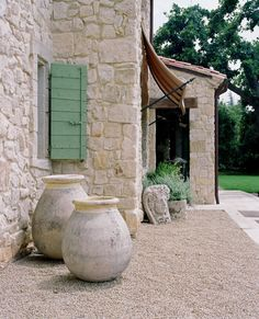 French Mediterranean patio. Love the big stone vessels.