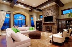 family room - stone fireplace, exposed beams, dark stain molding