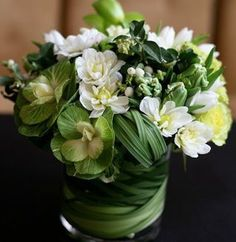 Dramatic and dense green and white floral arrangement in leaf wrapped vase - via the French Tangerine
