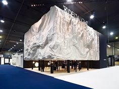 the unconventional display stand featured a monolithic boulder with a series of viewing holes arranged under a low ceiling in which the company's top products were displayed.