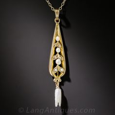 A lovely, long and slender tear drop shape pendant centered with shimmering pearl studded leaves with a feathery freshwater wing pearl dangling at the bottom. Circa 1900-1910. The drop measures 2 inches long, the chain measures 17 inches.