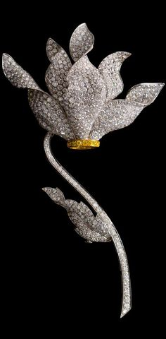 A Fine 18 Karat Gold, Colored Diamond and Diamond Flower Brooch, Ambrosi, in white gold with yellow gold accent, consisting of a blossom composed of five unfurling petals pave set with 516 round brilliant cut diamonds weighing approximately 25.80 carats total and 12 round brilliant cut yellow diamonds (origin of color not tested) weighing approximately 0.36 carat total, extending to the sty