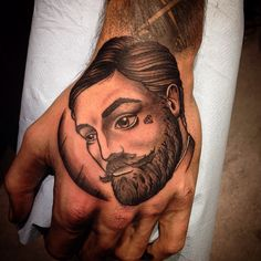 Hand tattoo of victorian gentleman with beard by fraserpeektattoo