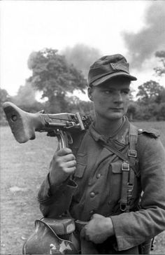 An MG42 machine gunner pauses for the Kriegsberichter cameraman in France while smoke rises in the distance.