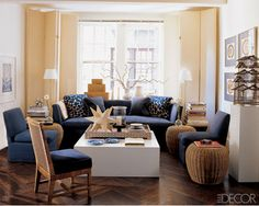 The walls are beige, and the navy comes in through the upholstery. Warm wood tones can be found in the accent furniture and accessories. The dark floor keeps everything grounded. Like the porcelain collection, the seating is fairly traditional and mixes well with a very modern white coffee table.