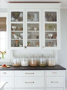 Love the large glass canisters and glass-front cabinets