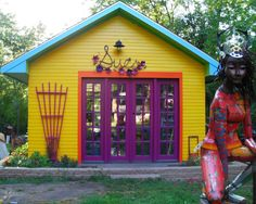 This is such a happy art studio!!!!  Little bright yellow house, purple French doors with orange trim, turquoise trim around roof, purple trellis, stone edging around flower gargen planted at foundation, bright sculpture of a woman in front yard