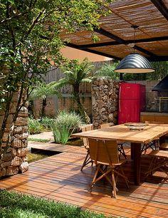 Na área gourmet, a pérgola tem cobertura de vidro temperado. Debaixo dele, réguas de bambu promovem um bonito e delicioso sombreado para curtir uma tarde de verão