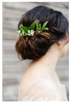 Splendid wedding hair updo! A loose low bun with flowers and greenery incorporating a garden feel!