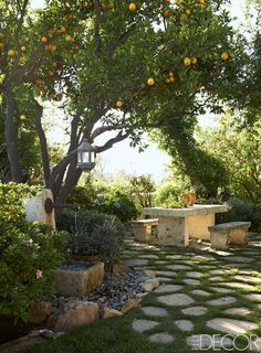 The garden, paved with reclaimed limestone, features an 18th-century French stone table originally used by fishmongers; the carved-stone benches are 19th century. - ELLEDecor.com
