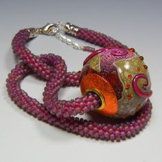 Large hollow, capped and cored lampwork glass bead on a seed bead necklace.